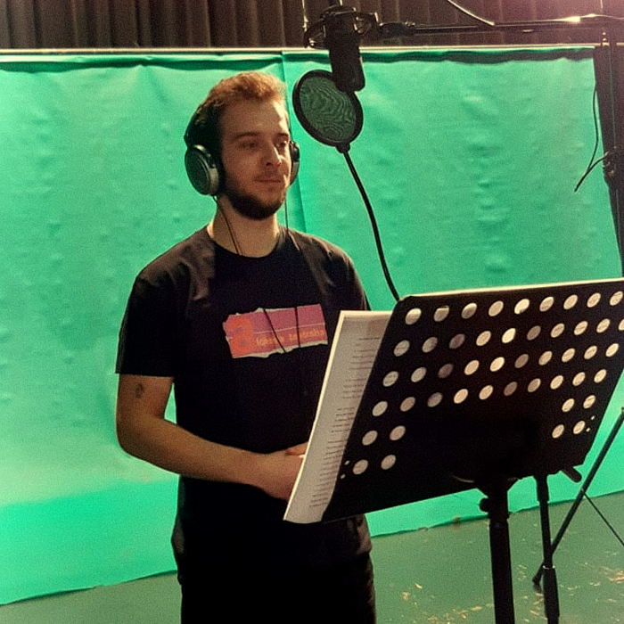 Miniaturka przedstawiająca chłopaka stjącego przed pulpitem nutowym i mikrofonem