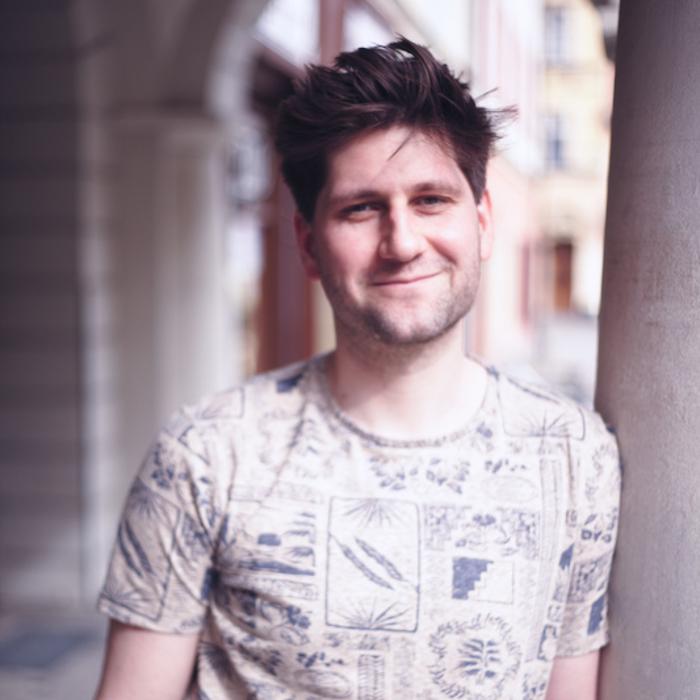 Mateusz Pakuła w jasnej koszulce pod arkadami ŚOK-u